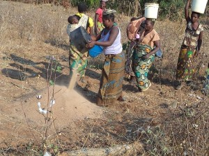Women contribute sand to the water Borehole pump